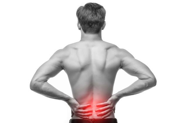 mann mit ischias beschwerden greift sich an den Rücken