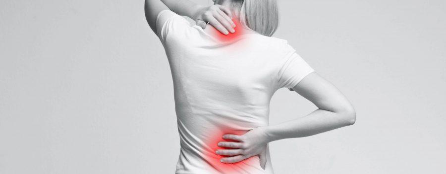 Frau mit Rückenschmerzen greift sich an den Rücken
