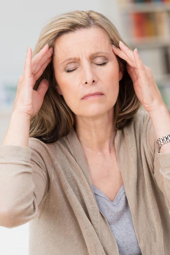 Frau mit psychosomatischen ursachen für rückenschmerzen fasst sich an den kopf