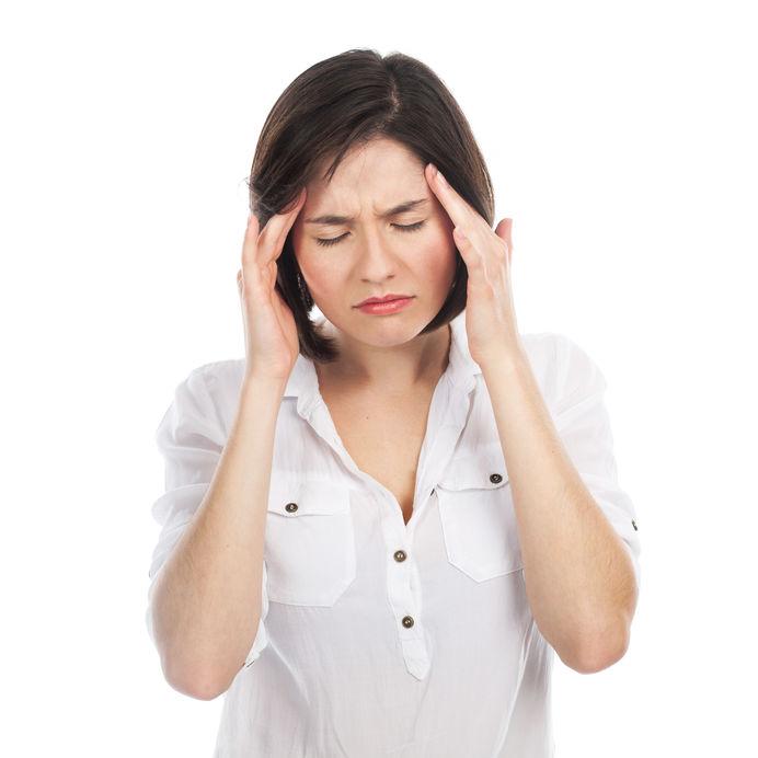 Frau mit psyschichen ursachen für rückenschmerzen fasst sich an den kopf