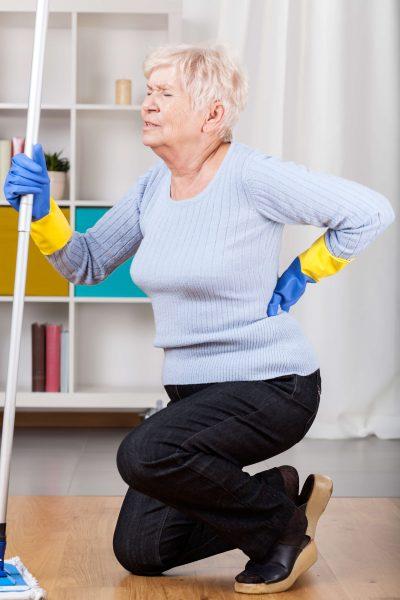 Putzfrau mit Rückenschmerzen kniet sich hin
