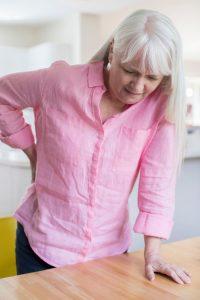 alte frau mit rückenschmerzen steht gerade auf