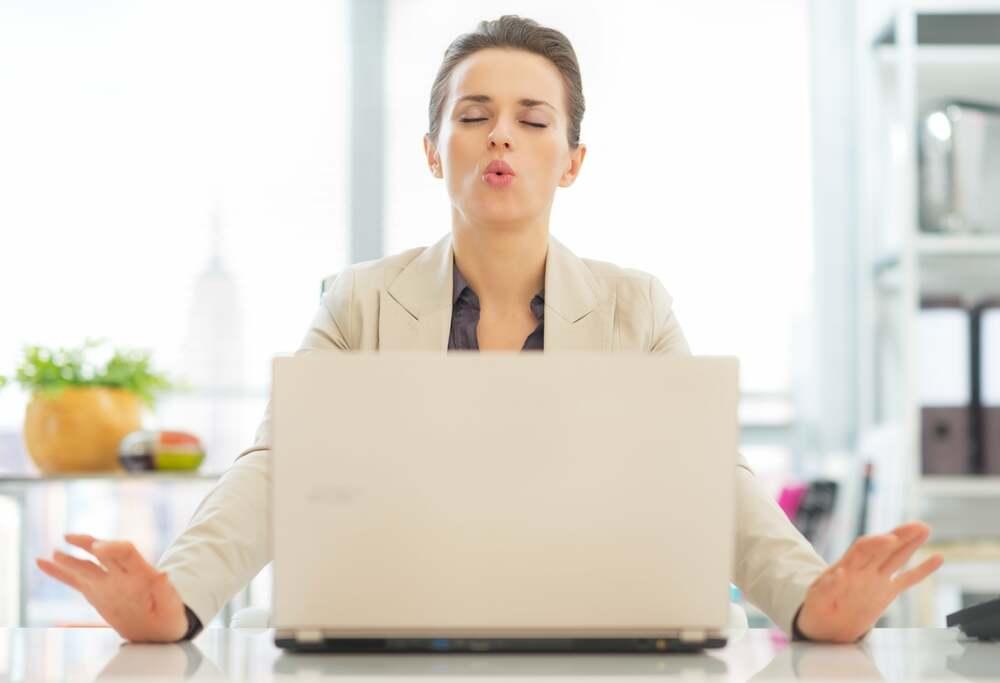frau macht atemübungen gegen rückenschmerzen im büro