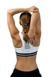 frau macht sport gegen rückenschmerzen und dehnt sich