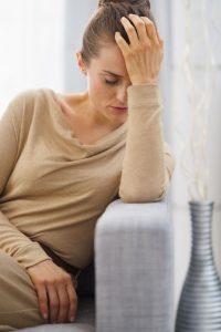frau mit rückenschmerzen mit der ursache verlust greift sich an den Kopf