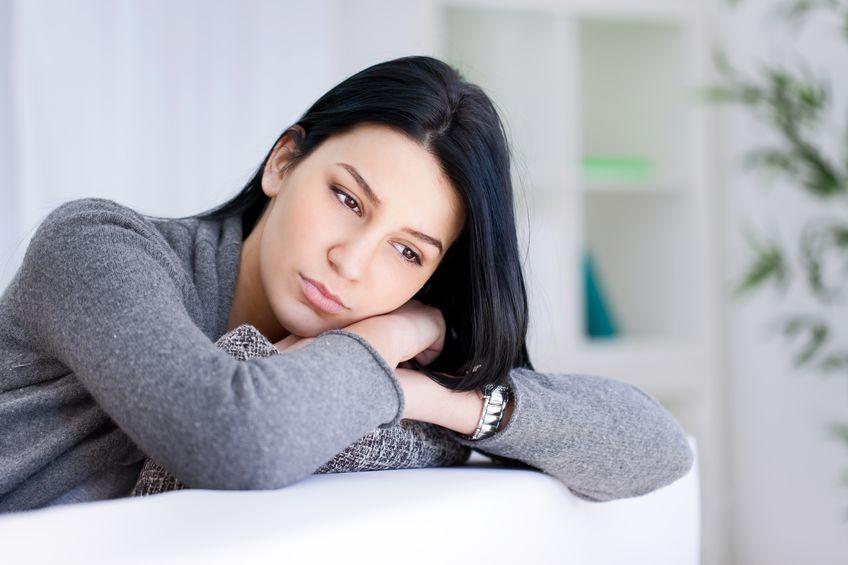 frau mit rückenschmerzen ursache ängste schaut auf den boden