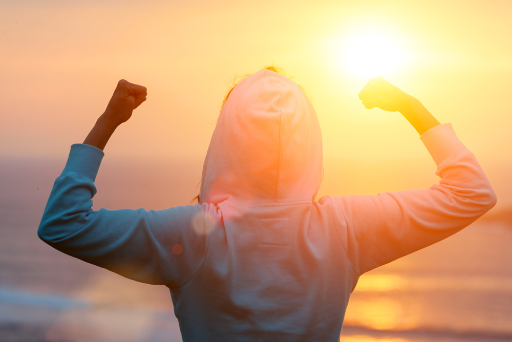frau mit siegespose gegen rückenschmerzen sieht untergehenden sonne entgegen