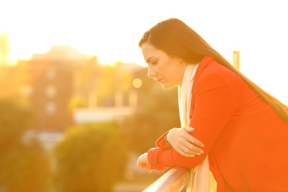 gestresste ffrau mit rückenschmerzen schaut nach unten im sonnenuntergang