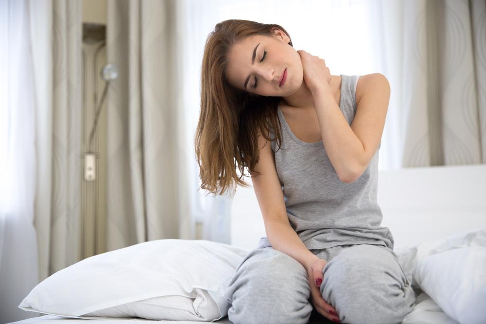gestresste frau mit rückenschmerzen greift sich an dne nacken während sie auf dem bett sitzt
