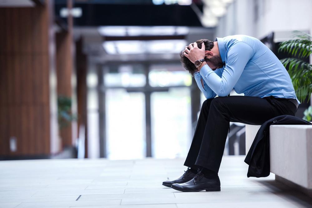 gestresster mann mit rückenschmerzen sitzt auf der bank