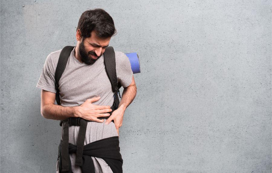 mann auf reisen mit rückenschmerzen greift sich an den rücken