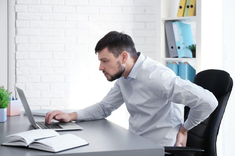 mann im Büro mit rückenschmerzen greift sich an den rücken