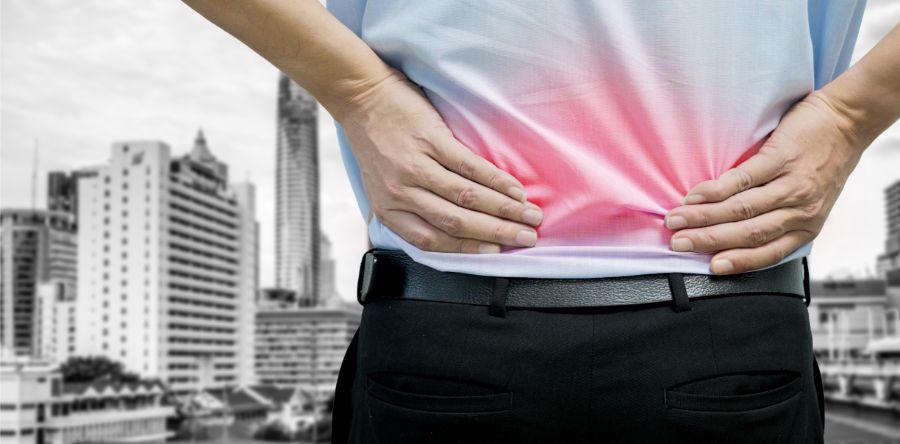 mann mit chronischen rückenschmerzen im hemd sieht auf stadt