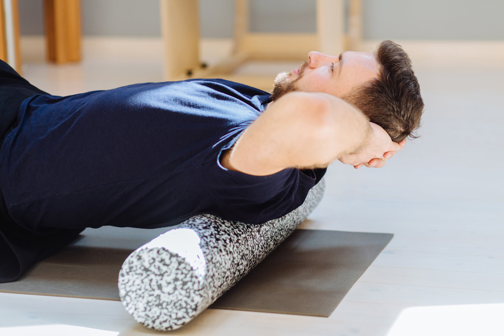 mann mit rückenschmerzen bereitet sich auf progressive muskelentspannubng und legt sich dabei hin