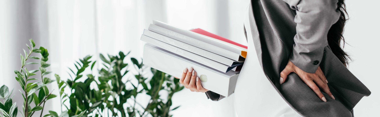 schwangere frau mit rückneschmerzen im büro