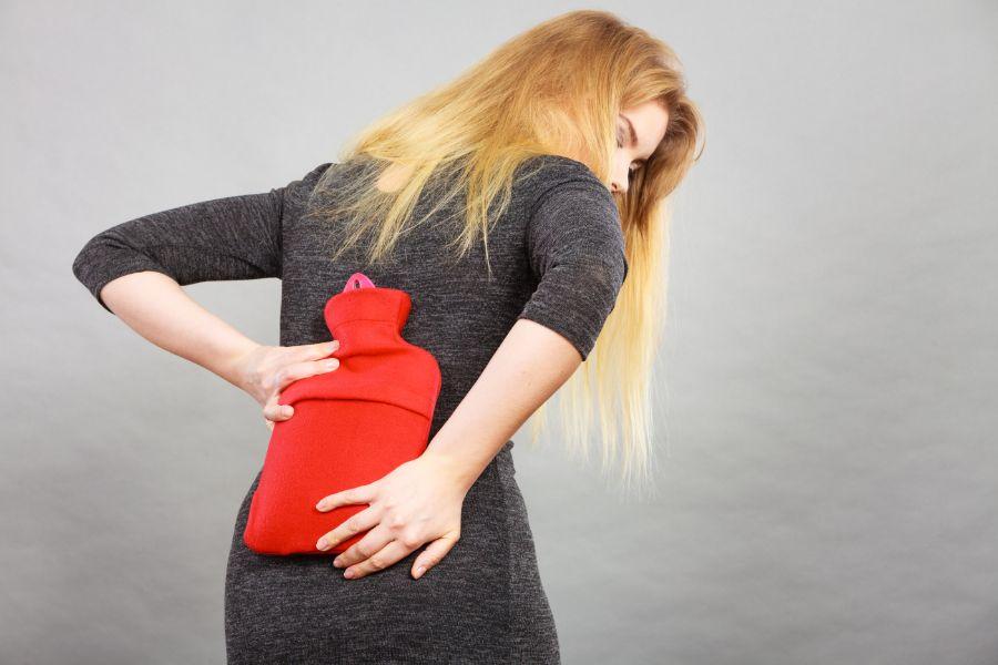 frau nutzt wärme im einsatz gegen rückenschmerzen